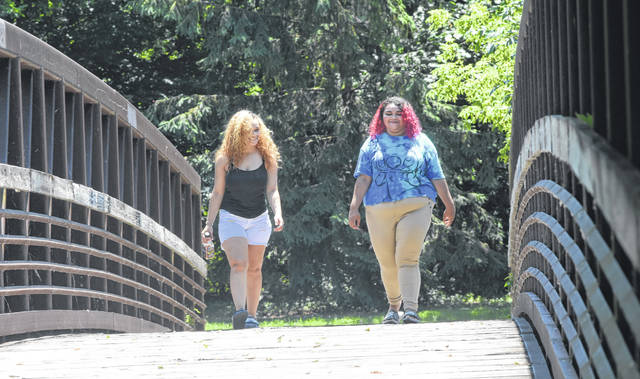 Lamaya Darby walks with her sister Nyesha down the Rotary River Walk to Faurot Park in Lima.