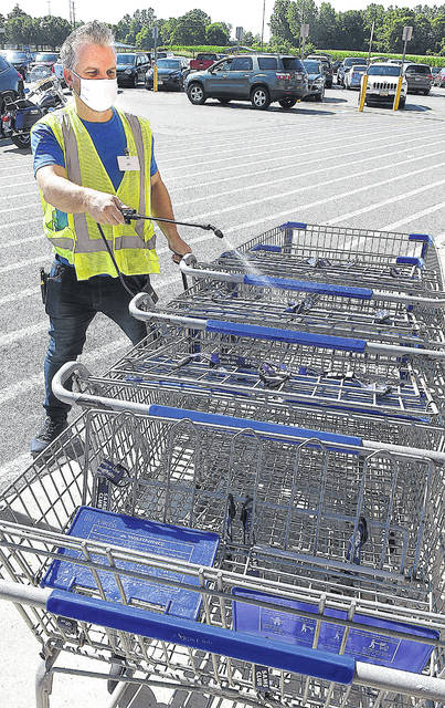 Dan Emmons, an employee at Sam's Club in Lima, sanitizes carts outside on Friday.