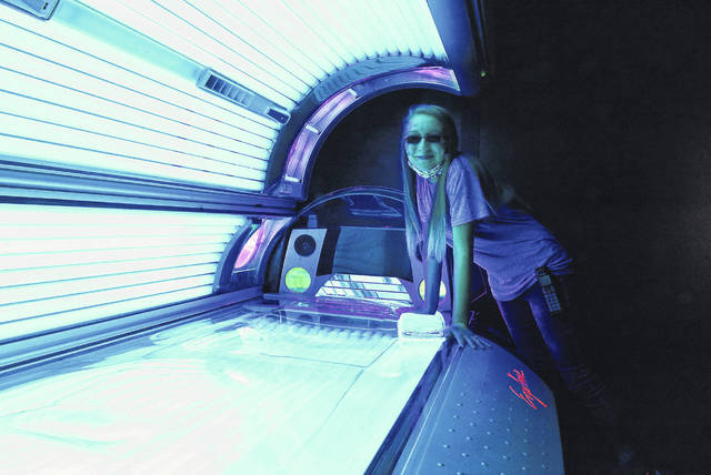 Trista Snider, an employee at Sun Central, next to a tanning bed.