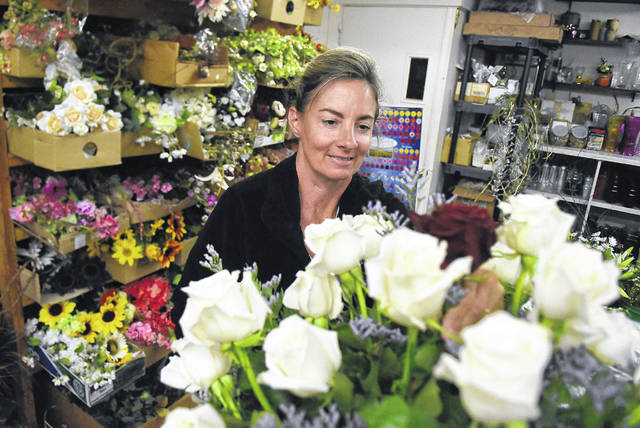 Stacy Miller, a florist at Town & Country Flowers, works on a floral design of roses.
