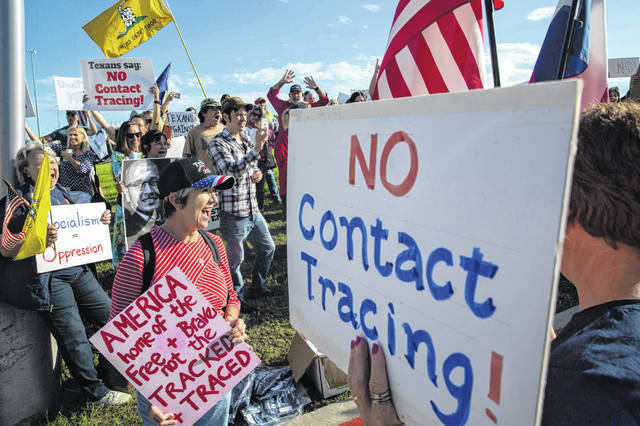 Renata Richardson, center, chants with other demonstrators during a protest organized by Texans Against Contact Tracing outside of the building that houses MTX Group, the company hired by Texas to do contact tracing, in Frisco, Texas, on Tuesday, May 26, 2020.