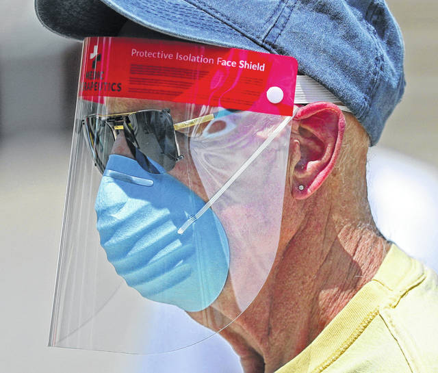 Phil Marcin, of Akron, wears a protective face shield and mask during a protest outside the University of Akron Student Union on Thursday. Gov. Mike DeWine ordered mandatory face masks in public places in seven counties labeled with a Level 3 public emergency in the midst of the coronavirus pandemic.