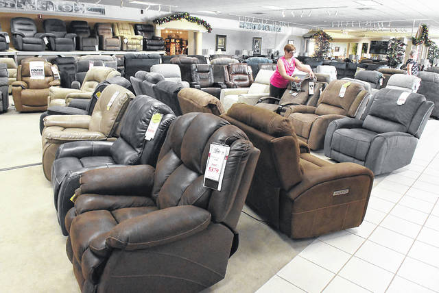 Kathy Pugh of Westrich Furniture & Appliances places new price tags on a group of recliners.