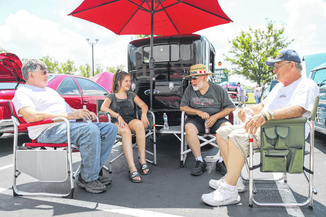 John Gunbar (left), Isabelle Buden, Garry Ricker and Tom Reese enjoy a conversation during the American Classics bike and car show at the Lima Harley Davidson on Saturday afternoon,