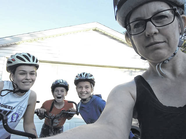 Ann Cox and her three children — Elena, Owen and Olivia — get ready for another leg on their bicycle trip.