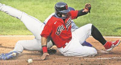 The Indians' Cesar Hernandez slides safely into home plate against Kansas City pitcher Brady Singer during Saturday's game in Cleveland. Hernandez scored on a wild pitch.