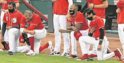 From left, the Reds' Phillip Ervin, Joey Votto, Amir Garrett and Alex Blandino kneel during the national anthem prior to Tuesday night's exhibition game against the Detroit Tigers at Great American Ballpark in Cincinnati.