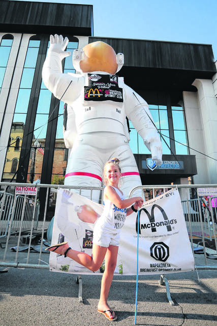 Seven year-old Addison Stinebaugh, of Wapakoneta, poses in front of the inflatable astronaut during last year's Summer Moon festival in downtown Wapakoneta.