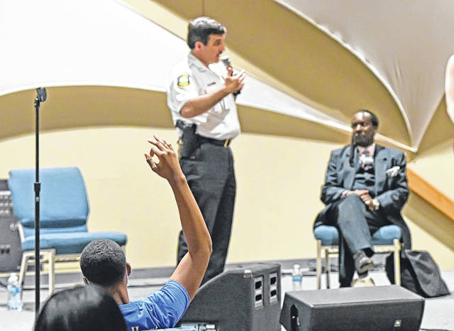 Attorney Jerry Pitts listens and Curtis Shannon Jr. raises his hand to ask a question as Lima Police Chief Kevin Martin addresses a Town Hall Meeting on Police Reform at The Impact Center in Lima on Thursday.