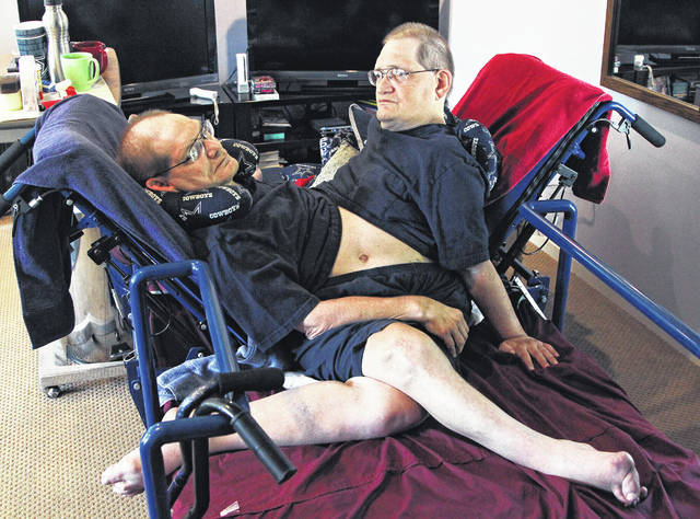 Donnie, left, and Ronnie Galyon sit inside their Beavercreek, Ohio, home, in a Wednesday, July 2, 2014 file photo. The world's longest surviving conjoined twins died on July 4, 2020, at the age of 68. Ronnie and Donnie Galyon of Beavercreek, Ohio, were born joined at the abdomen. In 2014, earned the distinction of being the world's oldest set of conjoined twins shortly before their 63rd birthday. (Drew Simon/Dayton Daily News via AP, File)