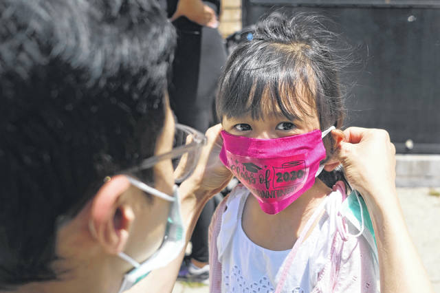 FILE - In this June 10, 2020, file photo, Olivia Chan's father helps her with a new mask she received during a graduation ceremony for her Pre-K class in front of Bradford School in Jersey City, N.J. School districts across America are in the midst of wrenching decisions during the summer about how to resume classes in settings radically altered by the coronavirus pandemic, with socially distanced school buses, virtual learning, outdoor classrooms and quarantine protocols for infected children as the new norm.