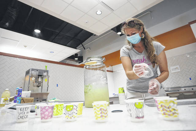 Alisha Frost of Nourish U Wellness Cafe passes out snacks at the grand opening of the newly remodeled YMCA on Saturday afternoon.