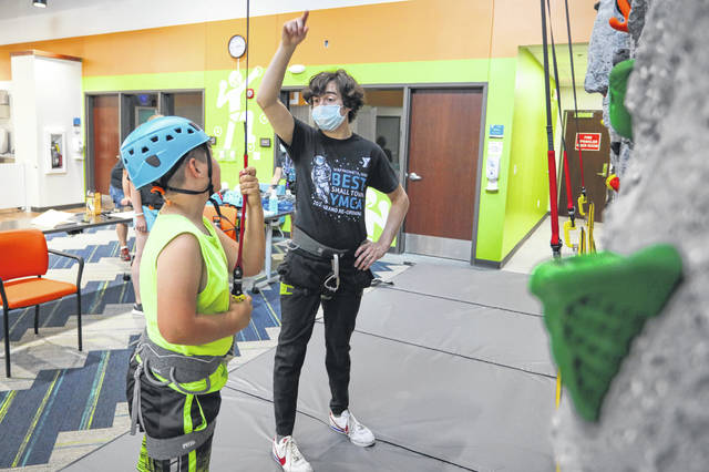 Liam Martell, of Wapakoneta, explains the rules of the new rock climbing wall to 9-year-old Joshua Lee, of Cridersville, at Saturday's grand opening of the newly remodeled Wapakoneta Family YMCA. The facility showed off an $8 million expansion and renovation.