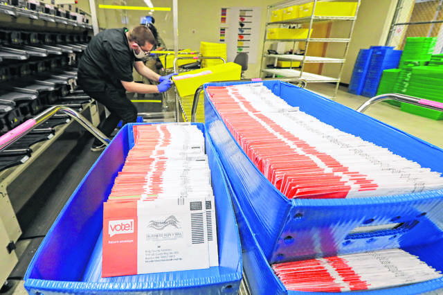 FILE — Vote-by-mail ballots are shown in sorting trays, Wednesday, Aug. 5, 2020, at the King County Elections headquarters in Renton, Wash., south of Seattle. Never in U.S. history will so many people exercise the right on which their democracy hinges by marking a ballot at home.