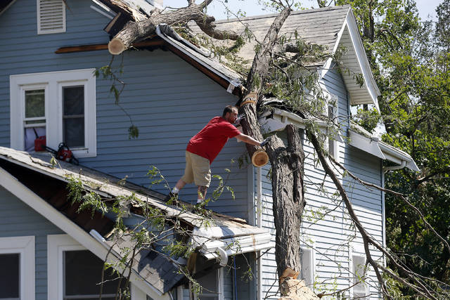 Mike Jacobis pushes a portion of tree trunk away as a neighbor helps on the ground in northwest Cedar Rapids, Iowa, on Wednesday. The tree, which fell in Monday's storm, fell and damaged Jacobis' porch and the roof over a second-floor bedroom and closet.
