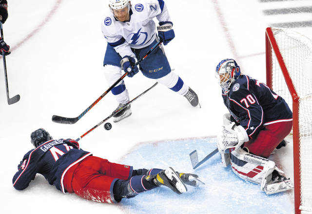 Columbus Blue Jackets defenseman Vladislav Gavrikov (44) goes down in front of goaltender Joonas Korpisalo (70) as Tampa Bay Lightning center Brayden Point (21) watches the puck during the third period in Game 4 of an NHL hockey first-round playoff series in Toronto on Monday, Aug. 17, 2020. (Frank Gunn/The Canadian Press via AP)