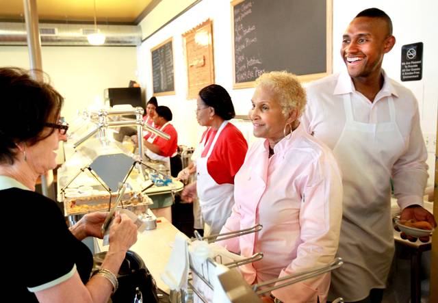 A customer picks up some to go food from Sweetie Pie's owner Robbie Montgomery, center, and Montgomery's son James Timothy Norman, right, at Sweetie Pie's in St. Louis on Tuesday, April 19, 2011. Norman, of Jackson, Miss., was arrested Tuesday, Aug. 18, 2020  in the March 14, 2016, fatal shooting of his nephew Andre Montgomery, who was gunned down near a park in St. Louis. (David Carson/St. Louis Post-Dispatch via AP)