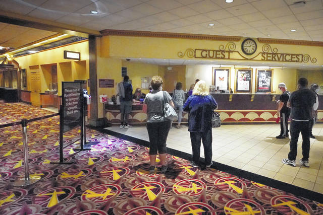 Patrons gather to get tickets for some of the first showings at the AMC theatre when it re-opened for the first time since shutting down at the start of the COVID-19 pandemic Thursday in West Homestead, Pa.