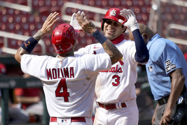 St. Louis Cardinals' Dylan Carlson, right, is congratulated by teammate Yadier Molina after hitting a two-run home run during the seventh inning of a baseball game against the Cincinnati Reds Sunday, Aug. 23, 2020, in St. Louis. (AP Photo/Jeff Roberson)