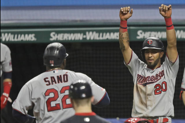 Minnesota Twins' Eddie Rosario (20) celebrates as teammate Miguel Sano (22) scores in the sixth inning of a baseball game against the Cleveland Indians, Monday, Aug. 24, 2020, in Cleveland. Sano hit a two-run home run and Rosario scored on the play. (AP Photo/Tony Dejak)