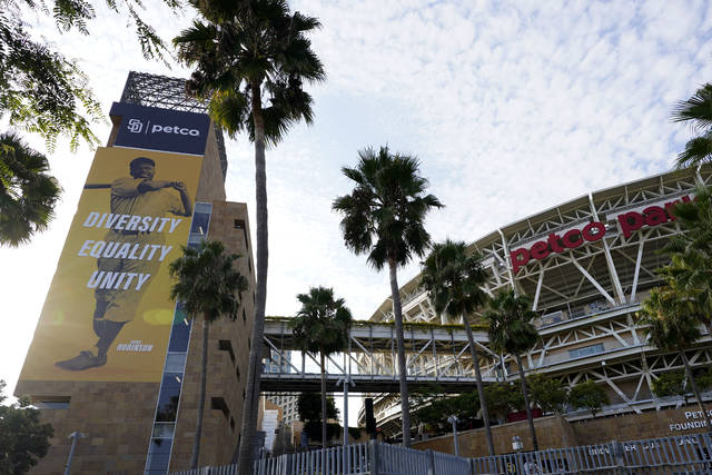 An image of baseball great Jackie Robinson hangs near Petco Park, where a baseball game between the San Diego Padres and the Seattle Mariners had been scheduled Wednesday, Aug. 26, 2020, in San Diego. Two Major League Baseball games have been postponed as players across the sports landscape reacted in the wake of the weekend shooting by police of Jacob Blake, a Black man, in Wisconsin. A pair of Major League Baseball games were postponed Wednesday as players across the sports landscape reacted in the wake of the weekend shooting by police of Jacob Blake, a Black man, in Wisconsin. Games between the Cincinnati Reds and Brewers in Milwaukee and the Mariners and Padres in San Diego were called off hours before they were set to begin. (AP Photo/Gregory Bull)