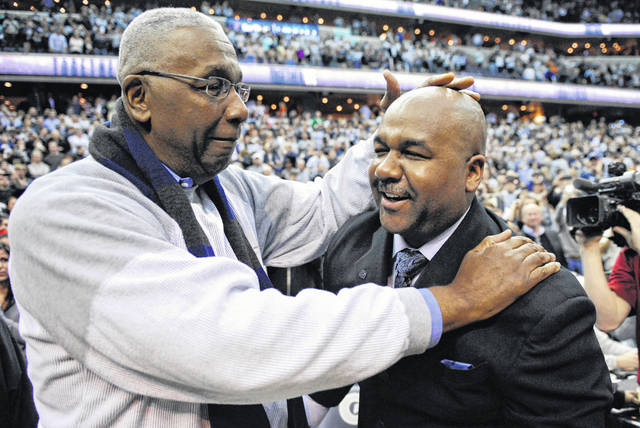 """FILE - In this March 9, 2013, file photo, former Georgetown coach John Thompson Jr., left, congratulates his son Georgetown head coach John Thompson III, right, after the Hoya's 61-39 win over Syracuse in an NCAA college basketball game in Washington. John Thompson, the imposing Hall of Famer who turned Georgetown into a """"Hoya Paranoia"""" powerhouse and became the first Black coach to lead a team to the NCAA men's basketball championship, has died. He was 78 His death was announced in a family statement Monday., Aug. 31, 2020. No details were disclosed. (AP Photo/Nick Wass, File)"""