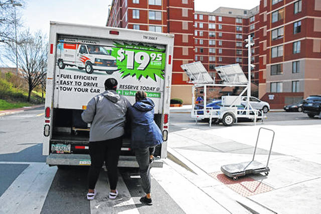 Students finish loading belongings into a U-Haul truck as they move out of their dorm in Washington in March. Moving is stressful enough without throwing a pandemic into the mix. If you are considering moving, be prepared for things to work a little differently and plan ahead to make it less of a hassle.