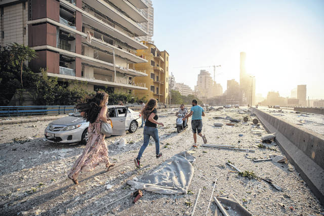 People run through an explosion scene in Beirut, Lebanon, Tuesday, Aug. 4, 2020. Blasts, damaged buildings and blew out windows and doors over a wide area as a giant mushroom cloud rose above the capital. Witnesses saw many people injured by flying glass and debris.