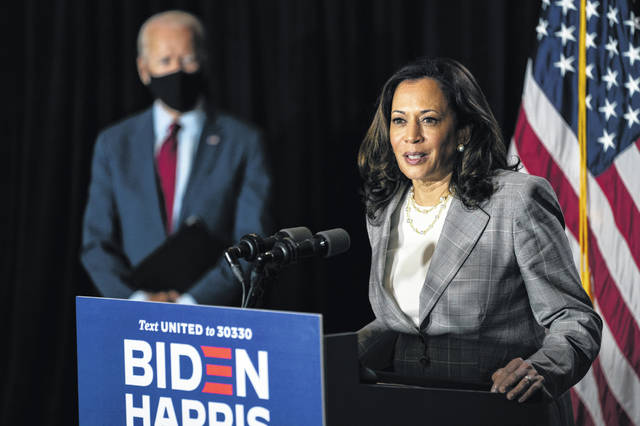 FILE - In this Thursday, Aug. 13, 2020 file photo, Democratic presidential candidate former Vice President Joe Biden stands at left as his running mate Sen. Kamala Harris, D-Calif., speaks at the Hotel DuPont in Wilmington, Del.