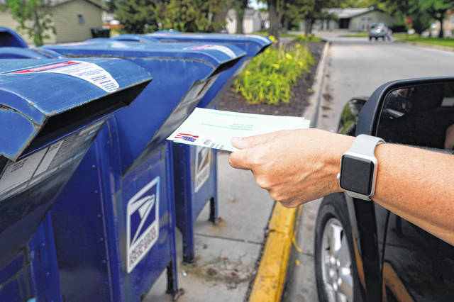 FILE - In this Tuesday, Aug. 18, 2020, file photo, a person drops applications for mail-in-ballots into a mail box in Omaha, Neb.