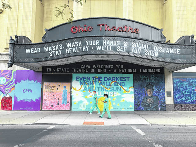 Workers in scrubs and masks walk past the Ohio Theatre in Columbus, Ohio, Wednesday, Aug. 26, 2020, amid the coronavirus pandemic.