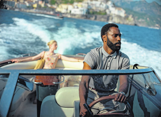 """This image released by Warner Bros. Entertainment shows Elizabeth Debicki, left, and John David Washington in a scene from """"Tenet."""""""