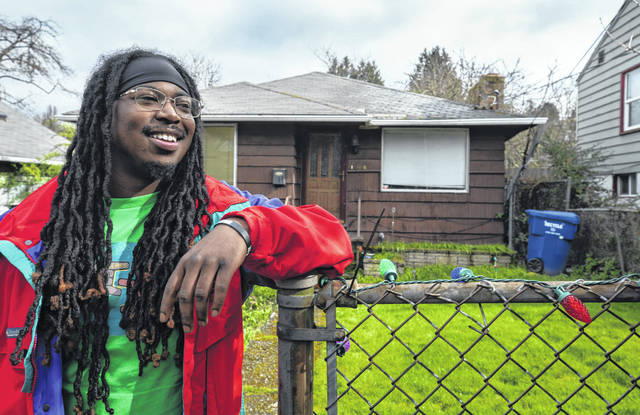 Andrese Collins, 24, stands at the front gate of the home where he grew up with his grandmother in Seattle's Central District in February. They moved to South Seattle when he was a teenager, but he's now getting a chance to move back to the Central District at Jackson Heights, a new affordable housing project, on his own.