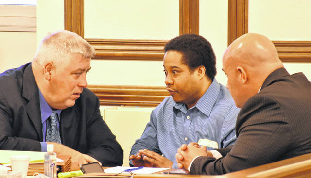 Quintel Estelle, center, the Lima resident charged in the 2019 shooting death of Donald Smith outside a Brice Avenue residence, confers with his attorneys during the second day of his murder trial Wednesday in Allen County Common Pleas Court.