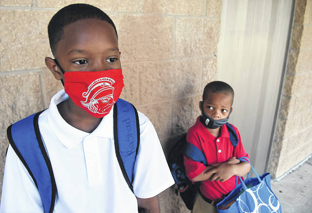Wearing masks, Rashad Lott, 9, waits outside Liberty Arts Magnet School in Lima with his younger brother, Kaden, 6, on the first day of school Wednesday. Rashad is in fifth grade, and Kaden is a first-grader.
