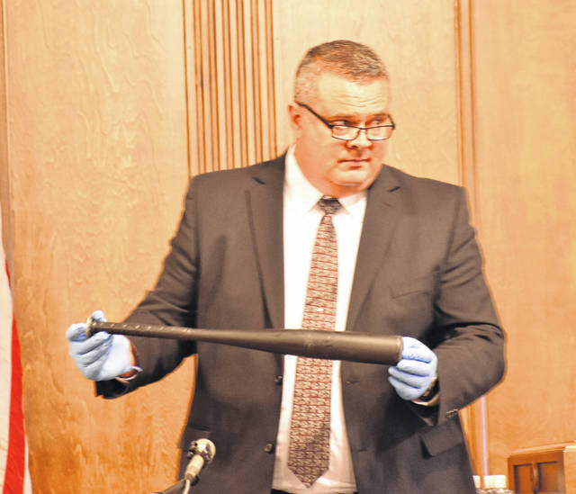 Greg Adkins, an identification officer for the Lima Police Department, shows the bat with which Scott Seitz struck Eric Glover during an altercation last year on West McKibben Street in Lima. Adkins said the bat was found in the back seat of a vehicle owned by Seitz.