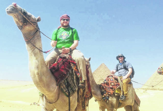 Justin Stuber (left), originally from Dunkirk, rides a camel in Egypt near the 4,500-year-old Giza Pyramids.