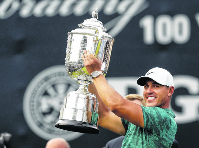 Brooks Koepka lifts the Wanamaker Trophy after winning the 2018PGA Championship golf tournament at Bellerive Country Club in St. Louis. He is trying to win his third consecutive PGA Championship this year.