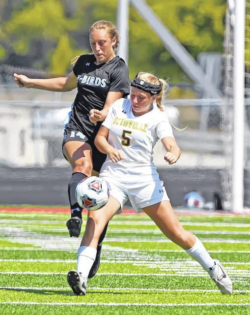 Lima Central Catholic's Olivia Stolly, left, and Ottoville's Kelly Jo Koenig compete for the ball during Saturday's match at Spartan Stadium.