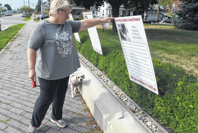 "A passerby and her dog checks out the Auglaize County Historical Society's ""Women's Story Walk,"" which highlights the accomplishments of more than a dozen women from west-central Ohio."