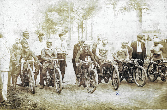"""Ralph Marshall participates in a motorcycle race in an unknown year. Marshall is marked with an X on the ground near the tire, and his shirt reads """"Excelsior."""""""
