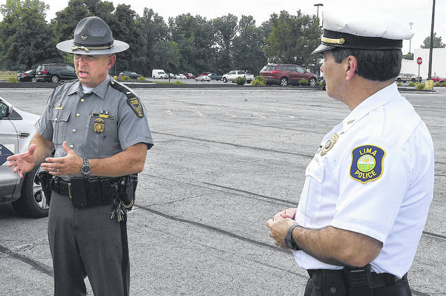 Ohio State Highway Patrol Lima Post Commander Lt. Tim Grigsby, left, addresses local media about increased traffic enforcement on Lima's west side alongside Lima Police Department Chief Kevin Martin while standing in a parking lot along Cable Road on Friday.