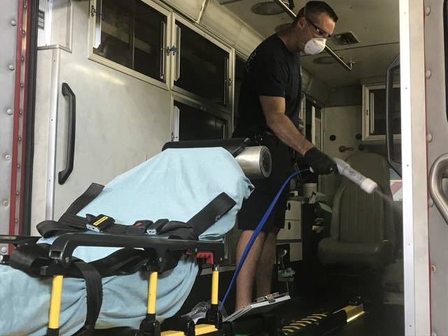Joe Seddelmeyer, a firefighter and paramedic with the Shawnee Fire Department, sprays down the back of a vehicle with the department's new electrostatic sprayer, a decontamination machine the fire department is using to keep staff and the public safe amid the coronavirus pandemic.