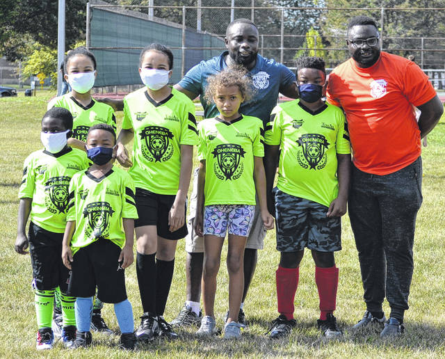 Members of the soccer team for ages 8 and younger from the Oheneba Soccer Academy pose at Saturday's soccer ball giveaway at the Safety City Soccer Field.