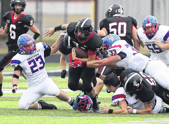 Spencerville's Gunner Grigsby fights for yardage against Crestview's Donovan Wreath (23) and Brody Brecht (33) while Crestview's Logan Gerardot loses his helmet during Friday night's Northwest Conference game at Spencerville. Check out more game photos at LimaScores.com.