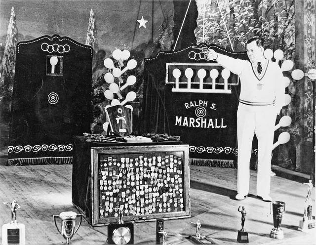Marshall poses for a photo with his display of awards related to shooting accuracy.