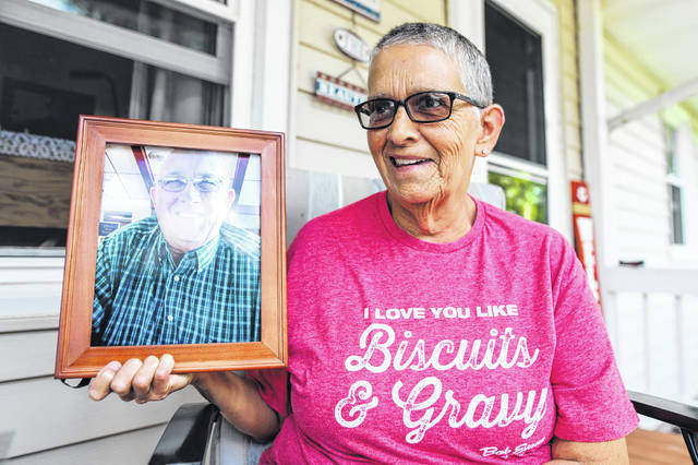 Tami Fullen holds a photograph of her late husband Ron at their residence in Wapakoneta. Fullen is now committed to advocating for residents of long-term care facilities, who she says are isolated, lonely and possibly neglected amid the pandemic.