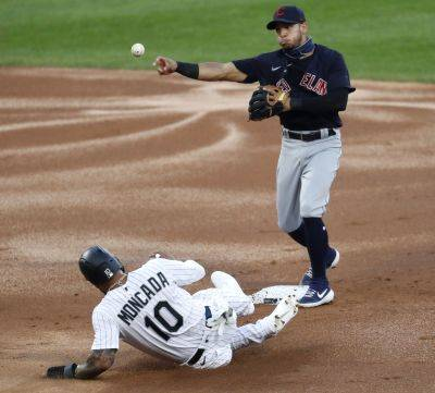 Cleveland's Cesar Hernandez turns a double play after forcing out the White Sox's Yoan Moncada at second base and getting Jose Abreu at first base during Friday night's game in Chicago. (AP photo)