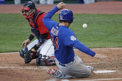 The Chicago Cubs' Anthony Rizzo scores as Indians catcher Sandy Leon can't hold onto the ball during Wednesday night's game in Cleveland. (AP photo)