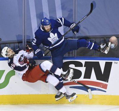 The Maple Leafs' Kyle Clifford checks Columbus' Dean Kukan during Tuesday's game in Toronto. (AP photo)